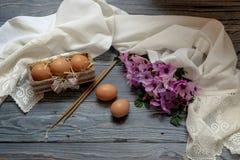 鸡蛋、狂放的银莲花属花束和教会蜡烛 库存图片
