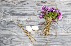 鸡蛋、银莲花属花束和蜡烛 免版税库存图片