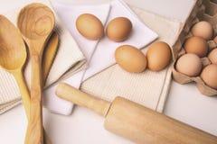鸡蛋和厨房工具顶上的看法在桌上 库存照片