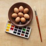 鸡蛋和油漆在桌上 免版税库存照片