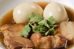 鸡蛋和猪肉在棕色沙司 库存图片