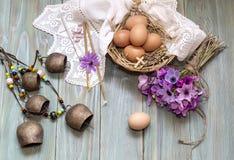 鸡蛋在一个柳条筐、狂放的银莲花属花束和教会蜡烛 免版税库存照片
