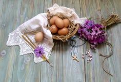 鸡蛋在一个柳条筐、狂放的银莲花属花束和教会蜡烛 免版税库存图片