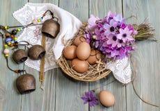 鸡蛋在一个柳条筐、狂放的银莲花属花束和教会蜡烛 免版税图库摄影