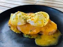鸡蛋本尼迪克特特写镜头用火腿和法式多士在一个黑色的盘子早餐 库存照片