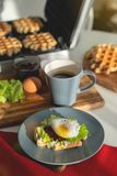 鸡蛋本尼迪克特用面包和蕃茄在一块板材用becon早晨三明治 库存图片