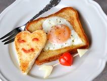 鸡蛋油煎了心形的多士 免版税库存图片