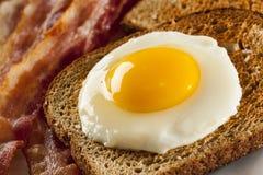 鸡蛋的有机Sunnyside用多士和烟肉 库存照片