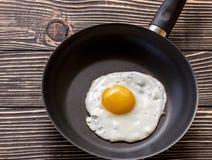 鸡蛋的油煎的晴朗的边在一个棕色老木板的一个平底锅 免版税图库摄影