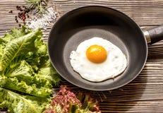 鸡蛋的油煎的晴朗的边在一个棕色老木板的一个平底锅 免版税库存照片