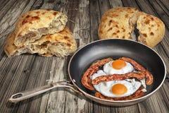 鸡蛋的晴朗的边煎用在老煎锅集合的烟肉更卤莽在被风化的庭院表上用两个皮塔面包被撕毁的大面包 库存图片
