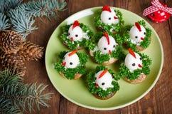 从鸡蛋的滑稽的鸡在与标志的圣诞节桌上 免版税库存图片
