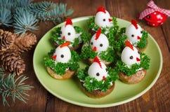从鸡蛋的滑稽的鸡在与标志的圣诞节桌上 免版税库存照片