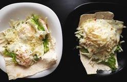 鸡蛋盘  荷包蛋用皮塔饼面包、莴苣和乳酪在一个白色和黑色的盘子 免版税图库摄影