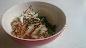 鸡蛋面用与绿色菜的烤猪肉脖子和蟹肉在白色木桌上的一个红色碗 免版税库存图片