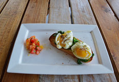 鸡蛋,在Toasted面包的菠菜用在边的加香料的切成小方块的蕃茄 库存照片