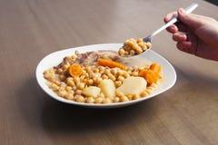 鸡豆炖用拿着吃的手一把匙子 免版税库存照片
