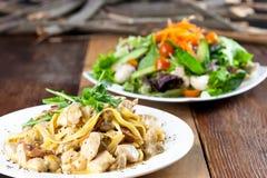 鸡面团和菜沙拉膳食在表上 免版税库存图片