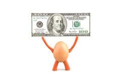 鸡鸡蛋拿着一百美元 图库摄影