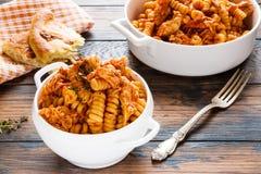 鸡fusilli意大利面食 烹调在从蕃茄的辣调味汁,葱,大蒜,烘干了牛至和麝香草、辣椒粉和橄榄油 免版税图库摄影