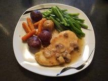 鸡marsala用土豆和青豆 免版税库存照片