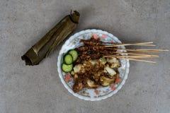 鸡satay街道食物盘完全与棕色甜花生调味汁、年糕切片和新黄瓜切片服务使用 库存照片