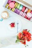鸦片开花花束和法国macarons与鲜美蛋糕和热奶咖啡在白色桌上 免版税库存照片