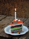 鸦片蛋糕片断与石灰奶油的和草莓结冻与一个被点燃的蜡烛 愉快的生日 选择聚焦 免版税库存照片