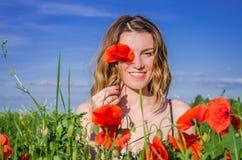 鸦片领域的一个年轻迷人的女孩在一个明亮的晴朗的夏日闭上与鸦片花的一只眼睛 免版税库存图片