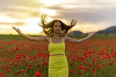 鸦片领域的美丽的女孩在日落 免版税图库摄影