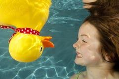 鸭子女孩水下一点橡胶的游泳 免版税图库摄影