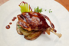 鸭子杵用土豆和大蒜烟肉调味汁 镀白色 鸭子confit 葡萄酒纸背景(被定调子-减速火箭的样式) 烤 库存图片