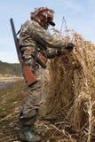 鸭子猎人做一个寻找的窗帘芦苇 免版税库存照片