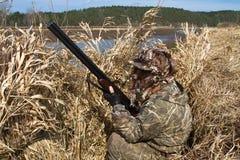 鸭子猎人在芦苇一个寻找的窗帘坐  免版税库存照片