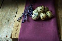 鹌鹑蛋和淡紫色枝杈在一块淡紫色亚麻布在谷仓木头,复活节 库存照片