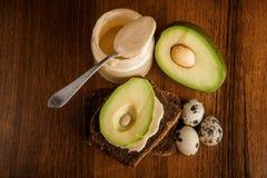 鹌鹑蛋顶视图,在黑麦面包,tahini瓶子的切的鲕梨 免版税库存图片