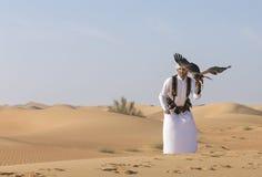 以鹰狩猎者在迪拜附近训练猎兔犬鹰在沙漠 免版税库存照片