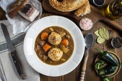 鹿肉猎人炖煮的食物和饺子用烟肉和葱 免版税库存图片