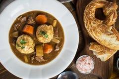 鹿肉猎人炖煮的食物和饺子用烟肉和葱 免版税库存照片