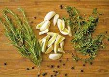 麝香草,迷迭香,大蒜,在木切板的胡椒 烹调新鲜水果厨房现代准备好的表对蔬菜 免版税库存照片