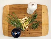 麝香草,迷迭香,大蒜,盐,在木切板的胡椒 准备好的厨师 免版税库存照片