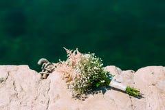 麦婚姻的新娘花束在岩石的由海 我们 免版税库存照片