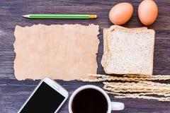 麦子、鸡蛋、老纸和咖啡的耳朵与面包片 免版税库存照片