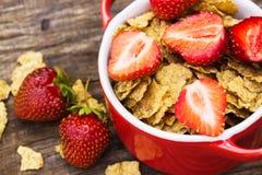 麦子剥落与在一个陶瓷罐的草莓片 免版税库存照片