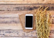 麦子和巧妙的电话在老木桌背景 免版税图库摄影