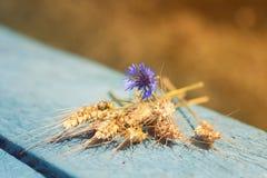 麦子和矢车菊的耳朵花束说谎在老桌上的 免版税库存照片