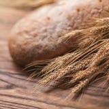 麦子和面包在木桌,浅DOF上 库存照片