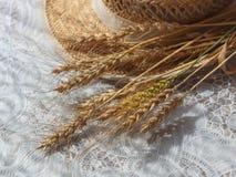 麦子小尖峰和草帽在白色桌上 免版税库存图片