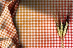麦子的耳朵在一张方格的桌布的 免版税库存照片