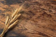 麦子的耳朵在木桌上的 库存图片